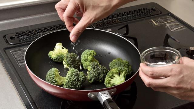 小房に分けたブロッコリーをフライパンに入れて塩をふる