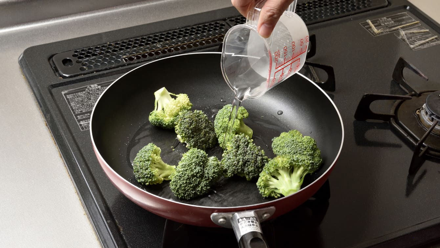 将100毫升水倒入盛有西兰花的平底锅中